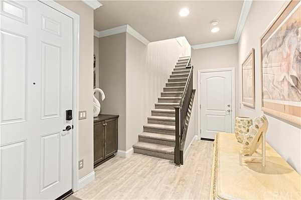 Photo #6 Formal Foyer with built in cabinets and powder room and door leading to attached garage.